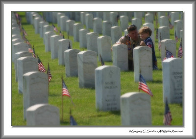 One of my personal favorites.  A father takes a moment to speak to his son about the sacrifice that was paid by so many in service to our country.  Memorial Day Grave Decoration, Dayton National Cemetery, Dayton, Ohio